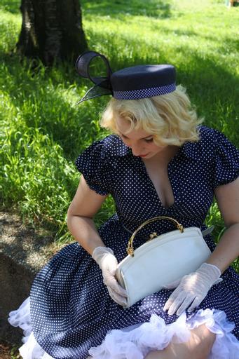 50er Jahre Frau mit weißer Tasche und Kleid mit passendem Hut